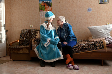 A volunteer talks to a resident of a nursing home during a visit on the occasion of the Christmas and New Year holidays in Omsk region