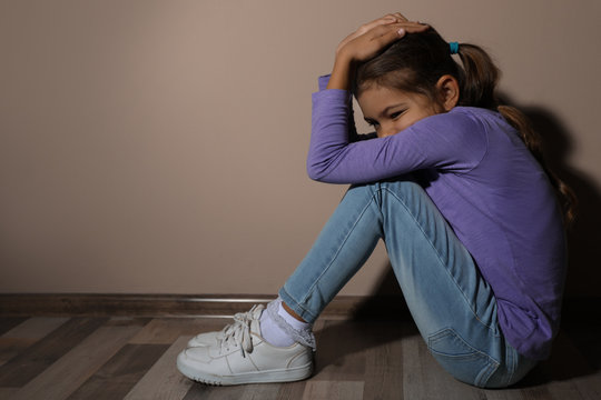 Scared little girl near beige wall, space for text. Domestic violence concept