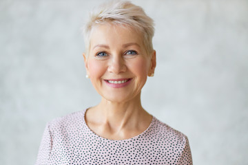 Fototapeta Close up image of good looking beautiful mature blonde female with blue eyes, elegant make upand pixie hairstyle smiling at camera, having confident happy facial expression, being in good mood obraz