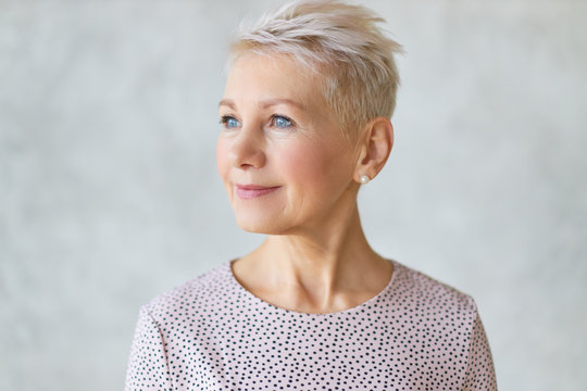 Close up studio image of beautiful attractive middle aged European lady with stylish haircut and neat make up looking away with confident smile posing isolated against marbled wall background