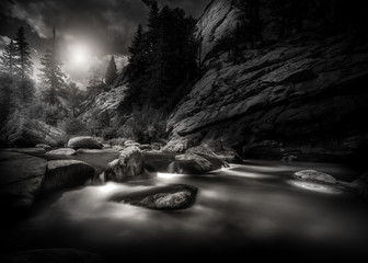 Foto op Canvas Zwart Black and white scene of a mountain river in the Rocky Mountains of Colorado. This is a long exposure so the river is smooth and silky looking.