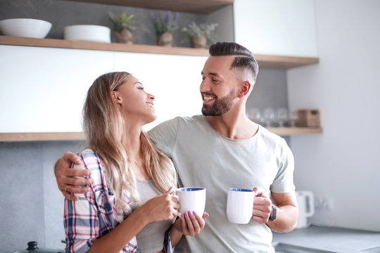 young couple drinking coffee standing in the kitchen