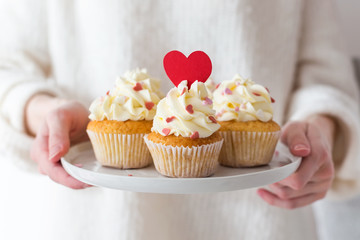 Valentine's Day. Sweet gift. Woman hands holding a plate with cupcakes decorated with hearts