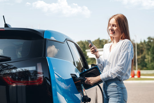 Transportation. Young woman on electric car having stop at charging station standing plugging cable browsing smartphone joyful while charging