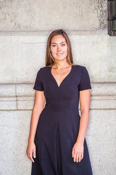 Portrait of Young East European Businesswoman in New York. Young woman with long brown hair, wearing black short sleeve, v neck dress, standing against wall on street, looking forward, smiling..