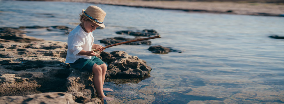 A little boy in a stylish hat sits on a stone and plays with a wand and water.