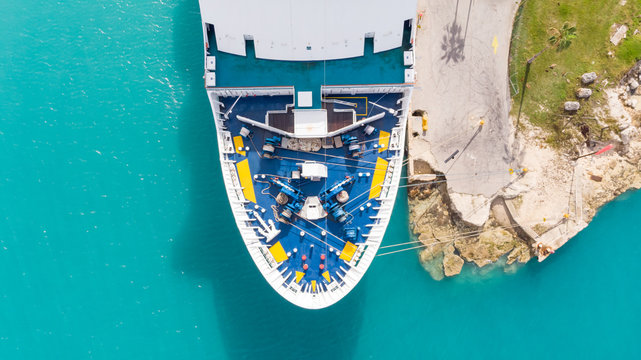 Aerial View on Grand Cruise Ship in Freeport in Grand Bahama. Drone view on Freeport landscape. Cruise Ship staying in port dock.