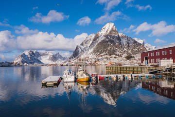 Dock in the winter season. The background is a high mountain with snow and the reflection on the water. Reine, Lofoten Islands, Norway.