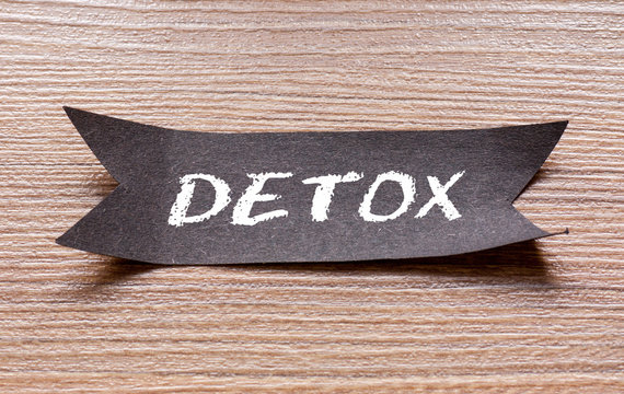 Detox word written on Black papper with wooden background