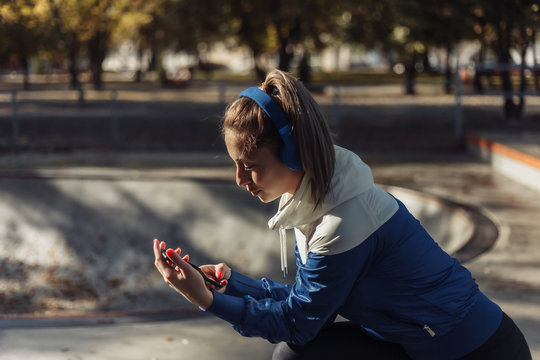 Young attractive sport woman in sportswear with headphones listens to music at sports park.