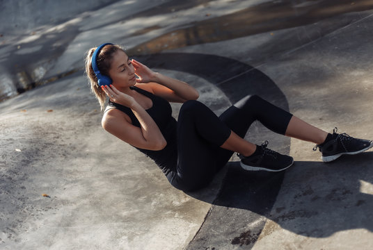 Attractive fit woman in sportswear listens to music with headphones while sitting in sports park