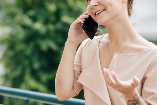 Cropped image of positive young woman gesturing when talking on phone outdoors