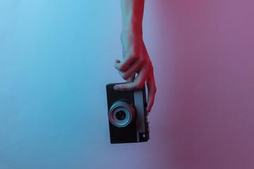 Female hands hold a retro camera. Creative pop art pink blue neon color. Trendy gradient illumination. Night light
