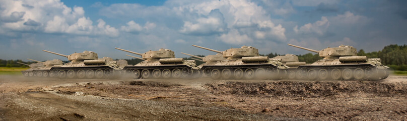 A troop of tanks rushing on a dusty road with the first row of tanks in focus