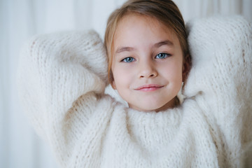 Portrait of a brunette little girl in white fluffy knitted sweater putting her hair in a pony tail....