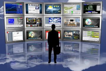 Uomo in silhouettedi fronte a serie di Tablet con varie applicazioni..