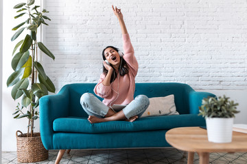 Motivated young woman listening to music with digital tablet while sitting on sofa at home.