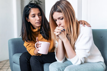Pretty young woman supporting and comforting her sad friend while sitting on the sofa at home. Fotomurales