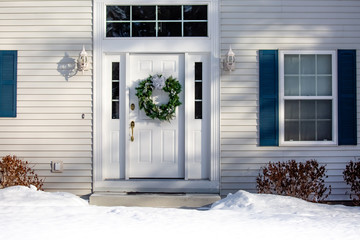 Front of a house  with a Christmas wreath on the front door in winter