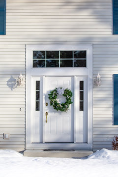 Front of a house  with a Christmas wreath on the front door in winter vertical