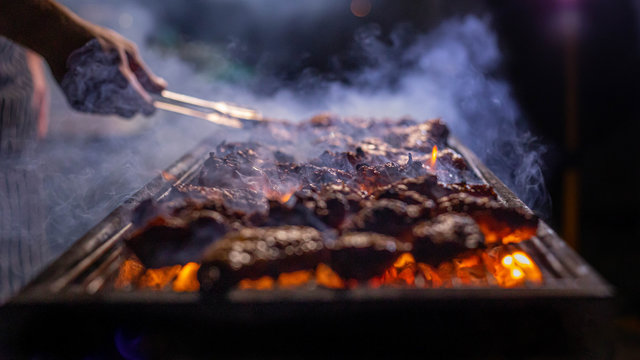 meat grilling  on fire with smoke