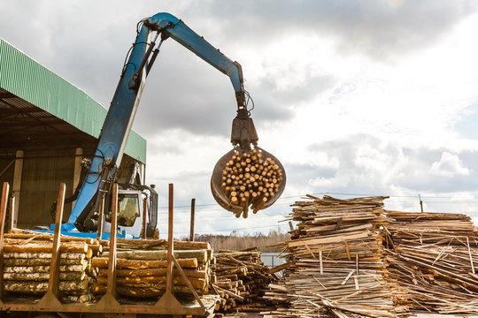 Log loader at lumber mill, sawmill. Front loader lifting stack of logs