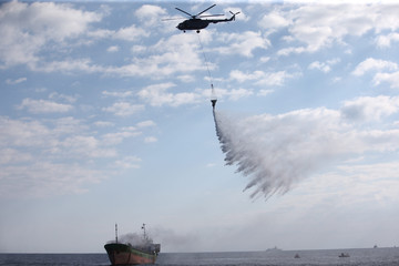 A fire chopper sprinkels water down on a boat in the Sea of Oman during the third day of joint Iran, Russia and China naval war games in Chabahar port, at the Sea of Oman