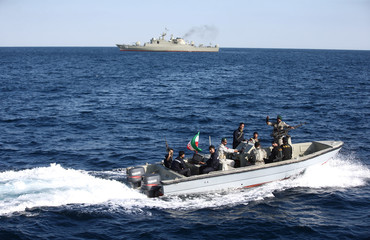 Iranian marine soldiers wave to the camera from a motor boat in the Sea of Oman during the third day of joint Iran, Russia and China naval war games in Chabahar port, at the Sea of Oman
