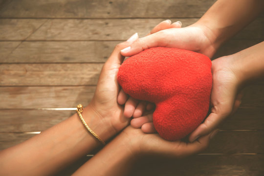 The hand of a beloved friend holding a red heart, health care, love, organ donation, family insurance and CSR concepts, World Heart Day, World Health Day