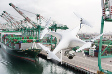 Unmanned Aircraft System Quadcopter Drone In The Air Near Large Shipping Vessel and Dock with Crates Wall mural