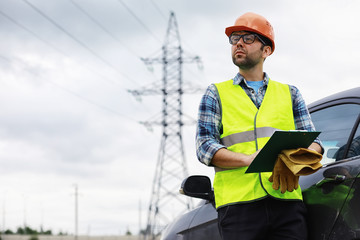 A man in a helmet and uniform, an electrician in the field. Professional electrician engineer inspects power lines during work.