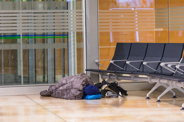 A backpacker waits for his next flight in the airport terminal and sleeps on the floor.