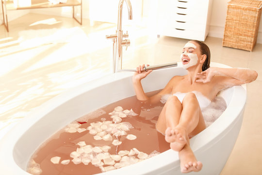 Beautiful young woman having fun in bathtub