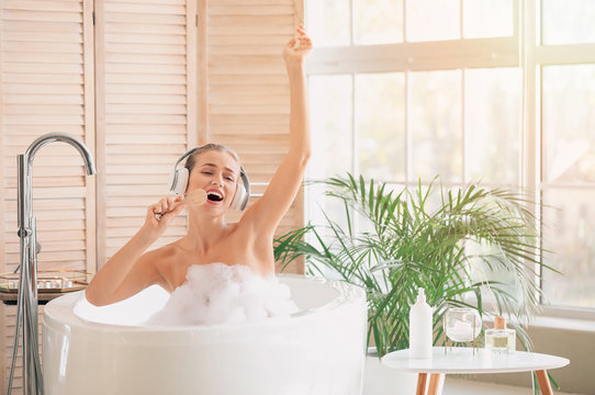 Beautiful young woman having fun in bathroom