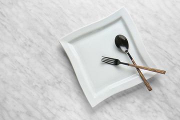 Empty plate and cutlery on light background