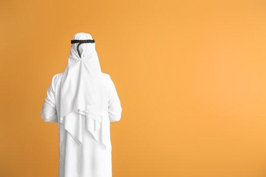Handsome Arab man on color background, back view