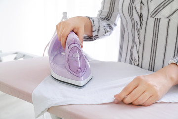 Woman ironing clean clothes at home, closeup