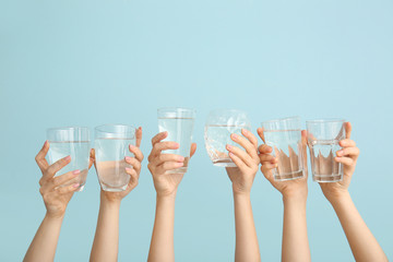 Female hands with glasses of water on color background