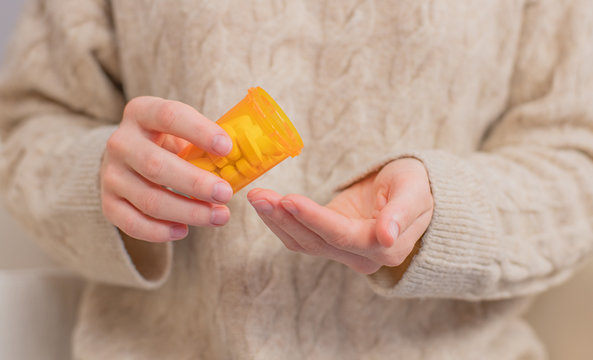 Woman takes pills vitamins. Woman is holding a jar of pills