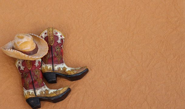 cowboy boots and hat laying on a textured brown background with writing space