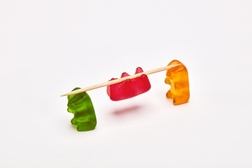 Two gummy bears carrying a gummy bear tied to a stick. Tribal carry concept.