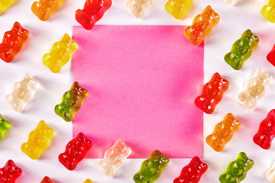 Flat lay design of gummy bear candies with a pink blank note paper
