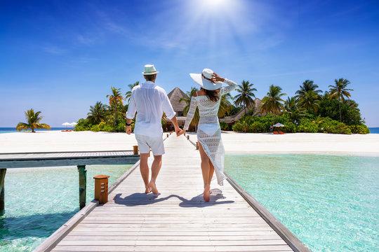 Ein glückliches Paar im Urlaub läuft händehaltend über einen Steg auf eine tropische Insel auf den Malediven zu