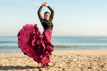 Young Spanish woman dancing flamenco on the beach