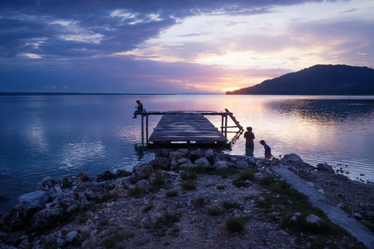 Sihouettes of people along pier with orange sunset on purple blue sky along lake Itza, El Remate, Peten, Guatemala