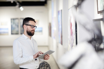 Waist up portrait of bearded art gallery manager using digital tablet while organizing exhibition in museum, copy space