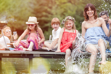 Smiling woman and daughter splashing water in lake while sitting on pier with family during summer picnic