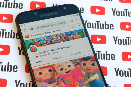 Cocomelon - Nursery Rhymes official youtube channel on smartphone screen on paper youtube background.