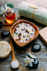 Natural spa cosmetics with essential massage oils, jasmine flower petals, zen stone on rustic wooden background. Handmade soap and herbal aromatherapy wellness treatment.