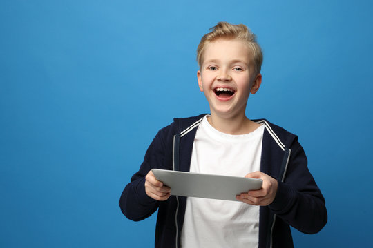 Smiling boy with a tablet. A child with a tablet. Portrait of a child on a colored blue background.